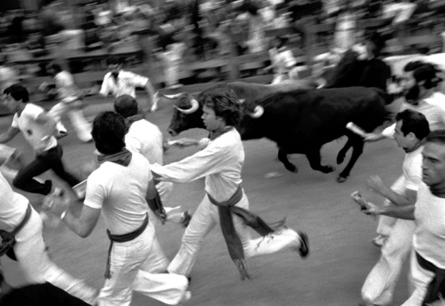 1980 - Pamplona, Spain. Running encierro at Telefonos. Joe and Antanasio - blurs from side. Photograph copyright 1980, Jim Hollander