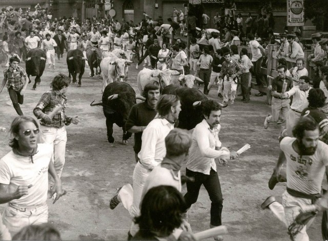 13 July 1973 - Pamplona, Spain - encierro at telefonos with Joe Distler (L-Madras shirt)  Matt Carney (Center, looking at bull) and Jim Hollander, right, in number 2 T-shirt, looking back at bulls.