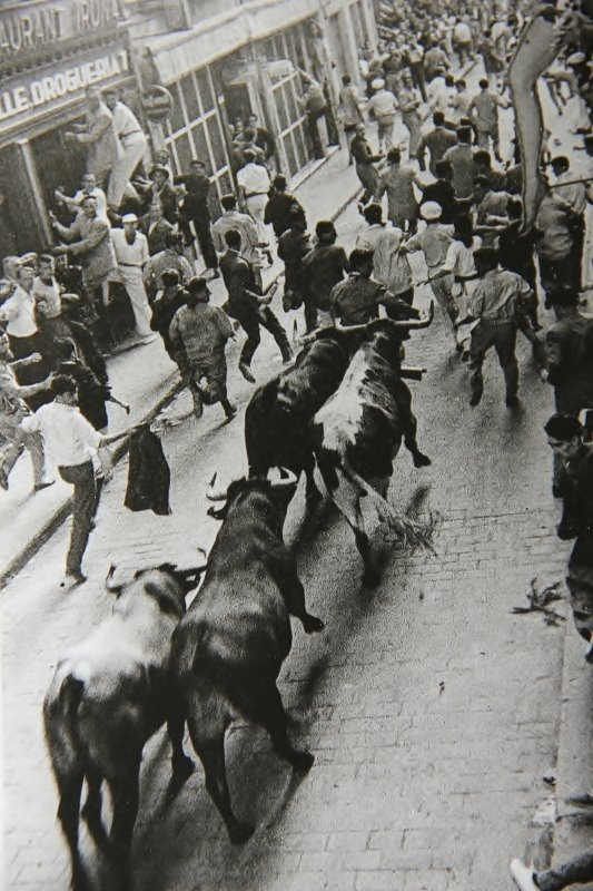 Matt Carney running in the centre of the street, on the horns of the bulls, in 1960